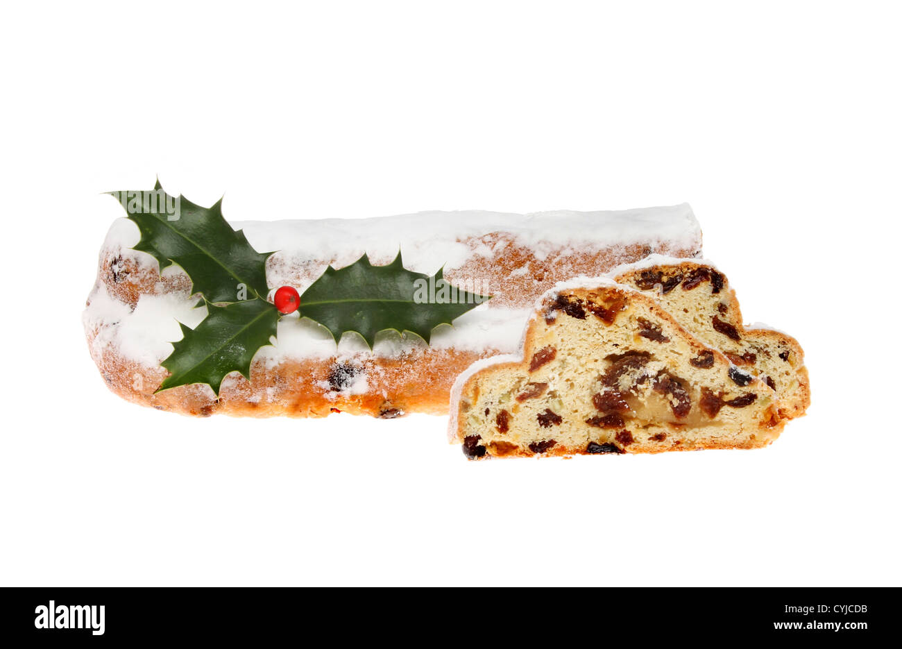 Icing sugar dusted Christmas stollen with slices cut and a sprig of holly isolated against white - Stock Image