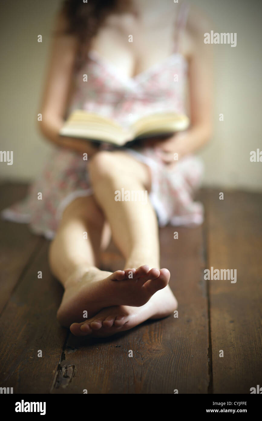 young woman reading a book on the old wooden floor - Stock Image