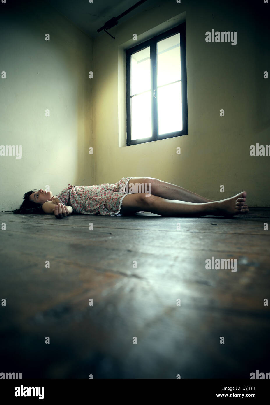 Dead woman lying on the wooden floor. Empty room - Stock Image
