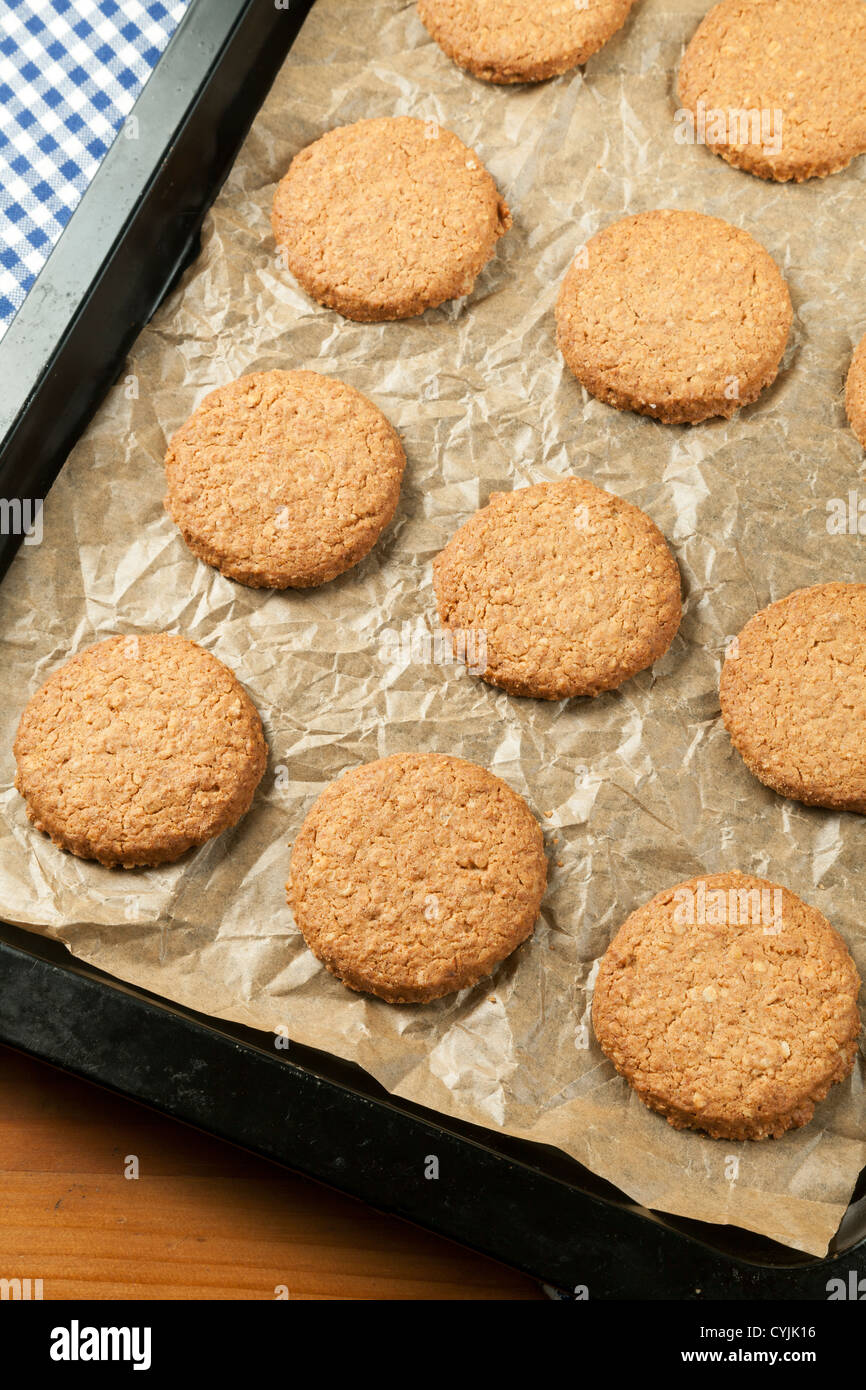 Oat biscuits on baking sheet freshly baked - Stock Image