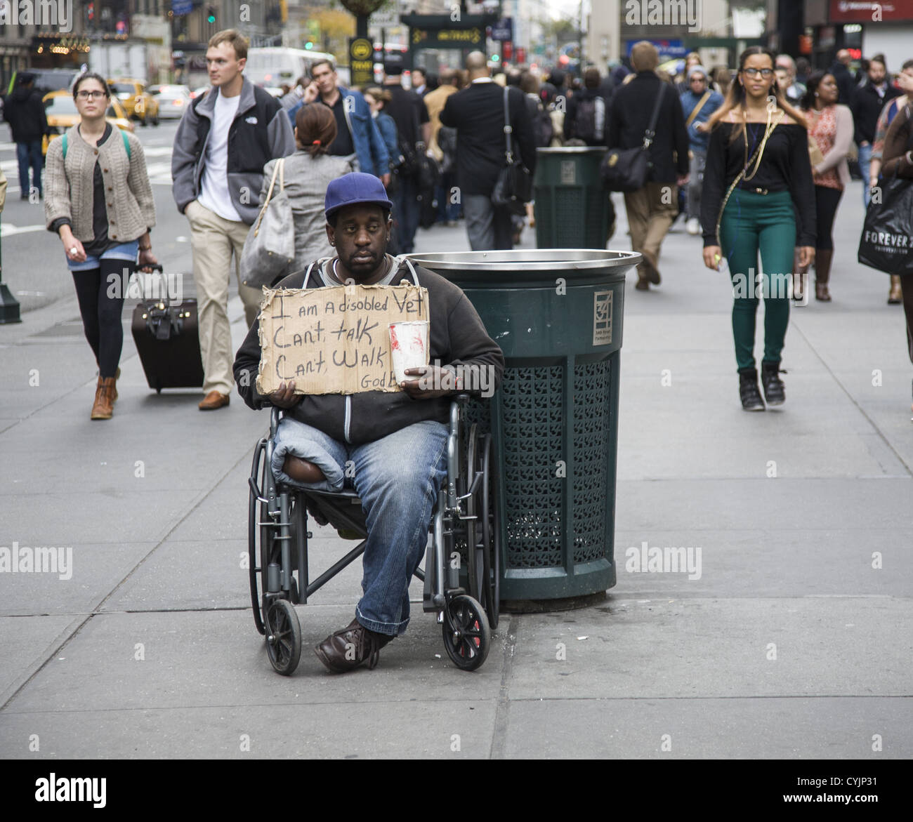 Disabled war veteran trying to raise some money on the street near Penn Station along 7th Avenue in Manhattan, NYC - Stock Image