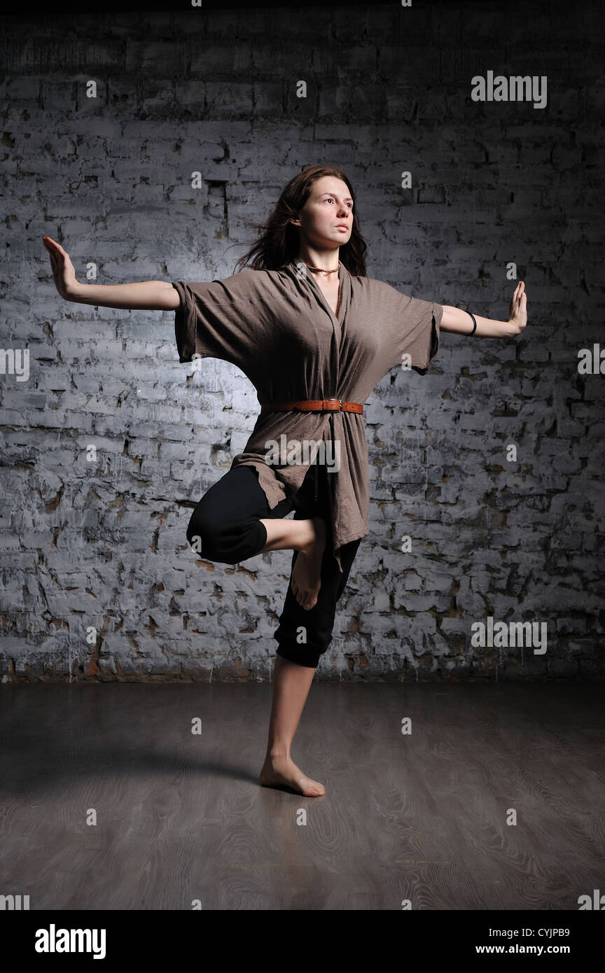 Full Length Portrait Of Young Beautiful Woman Doing Yoga Excercise Against A Brick Wall