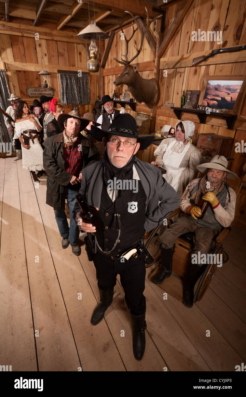 Tough sheriff with sad customers in old American west saloon - Stock Image