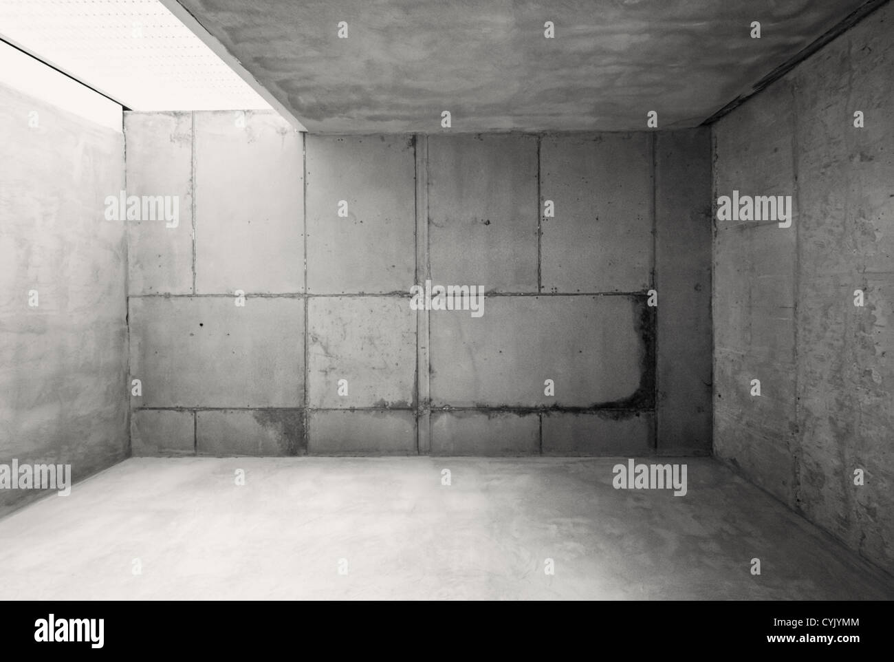 Empty warehouse room with concrete walls and floor. - Stock Image