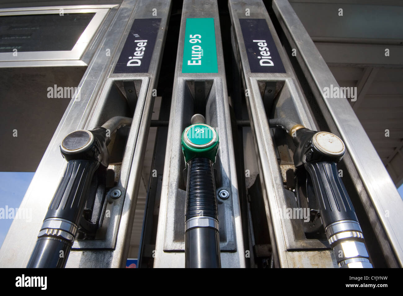 Three fuel nozzles at a gas station - Stock Image