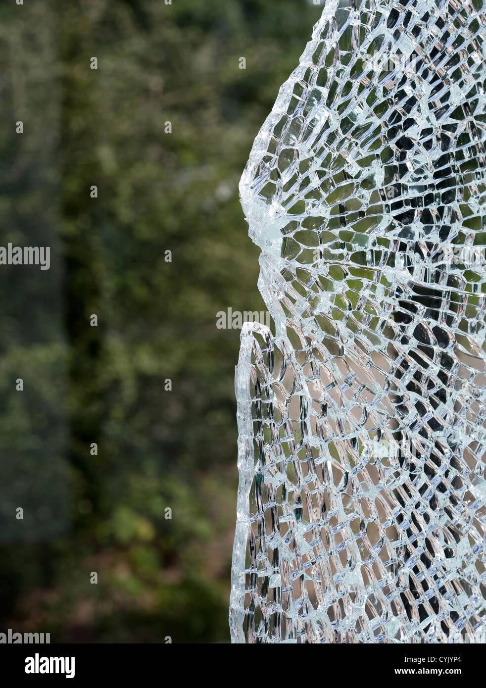 A broken window at a busstop caused bij vandalism - Stock Image
