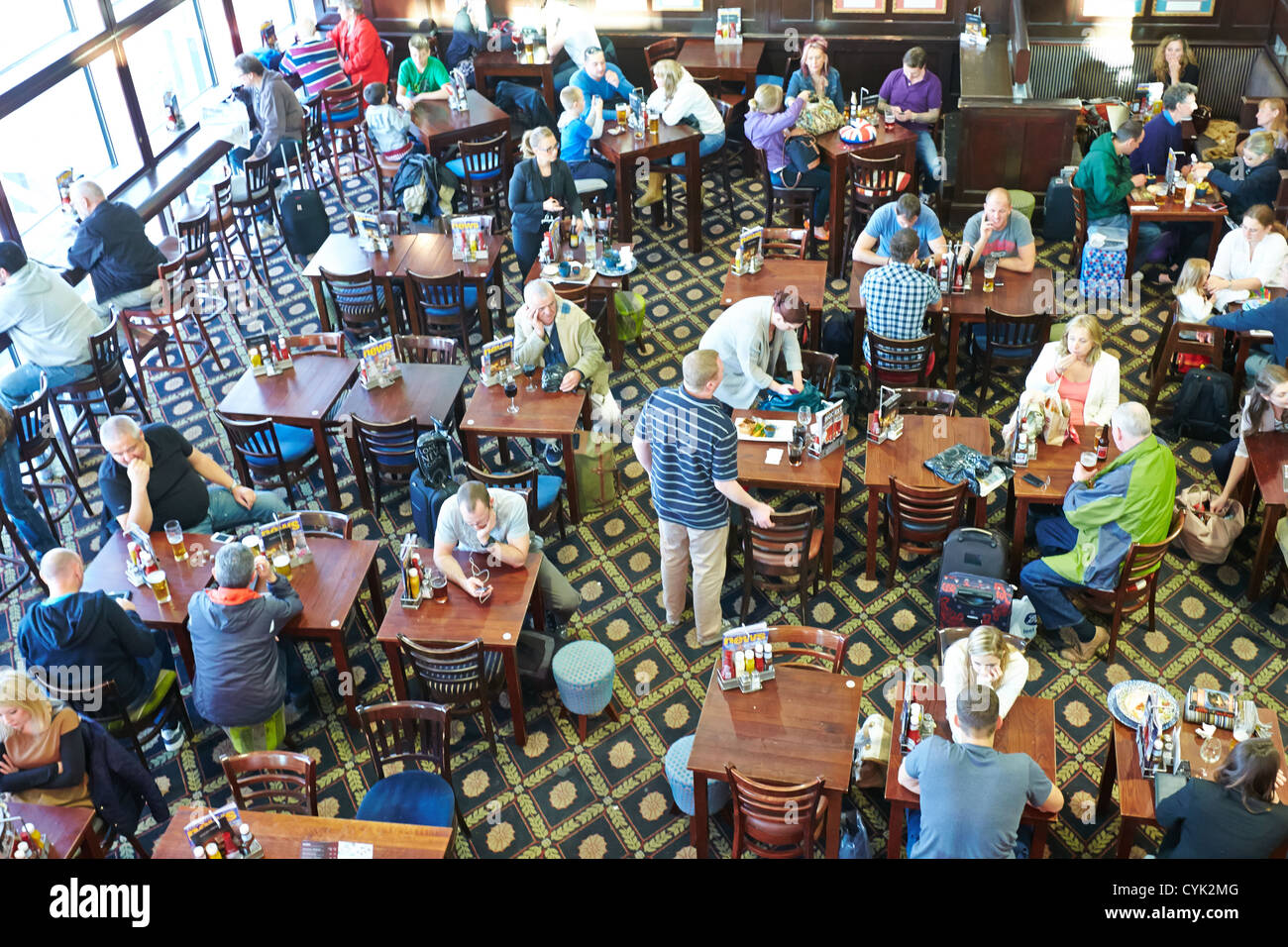 Passengers in the Red Lion bar, owned by JD Wetherspoons,  in the north terminal concourse at Gatwick Airport, London - Stock Image