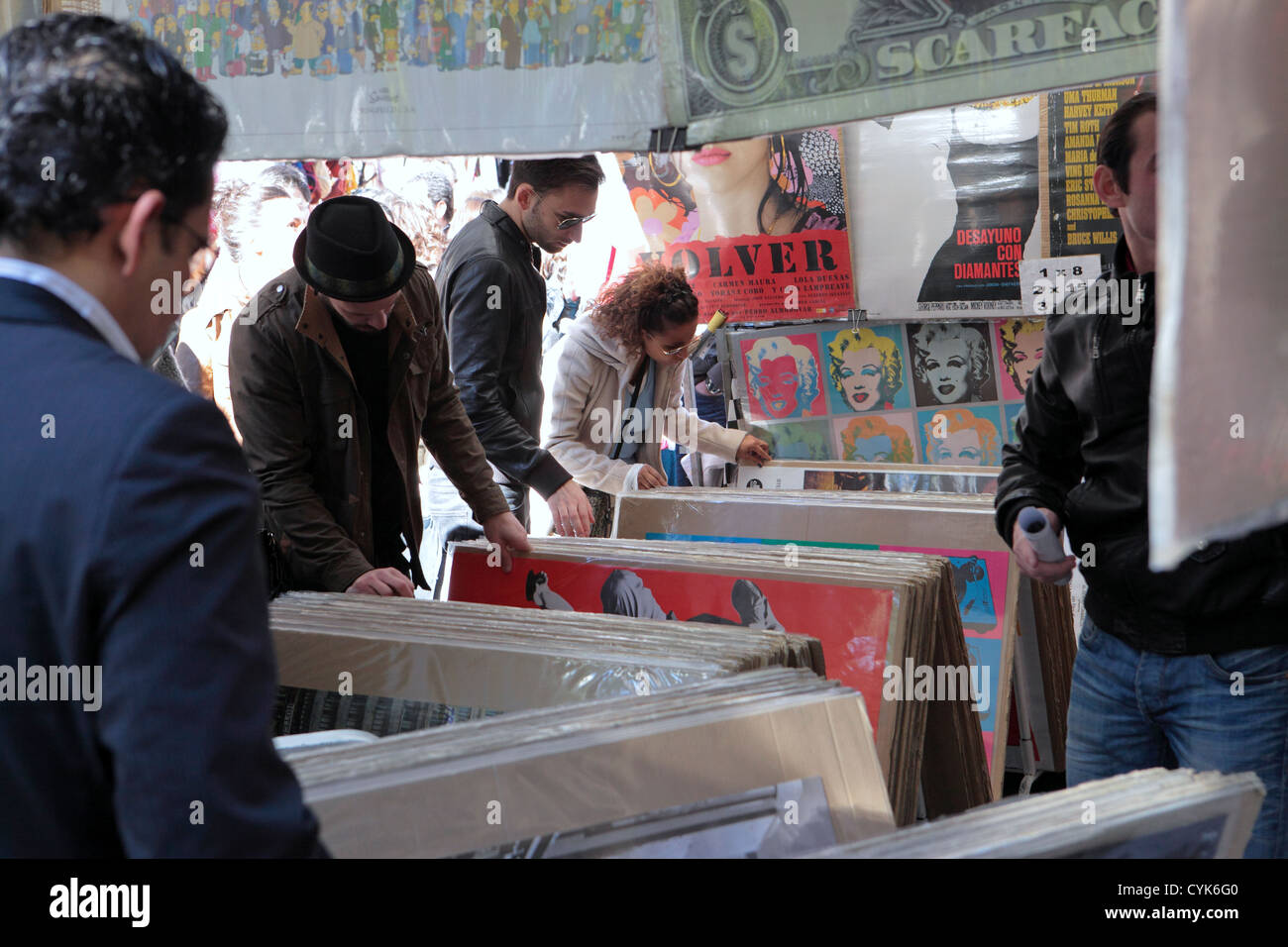Shoppers browsers flick through posters reproduction art works, flea market El Rastro Madrid, Spain - Stock Image
