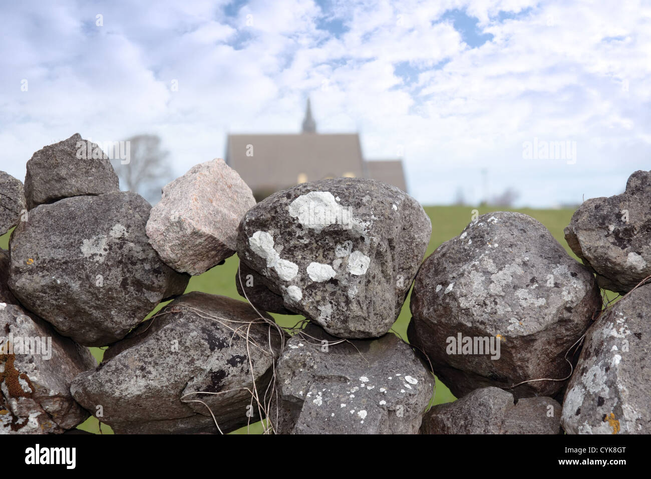 old stone wall with church in background in ballyvaughan county clare ireland - Stock Image