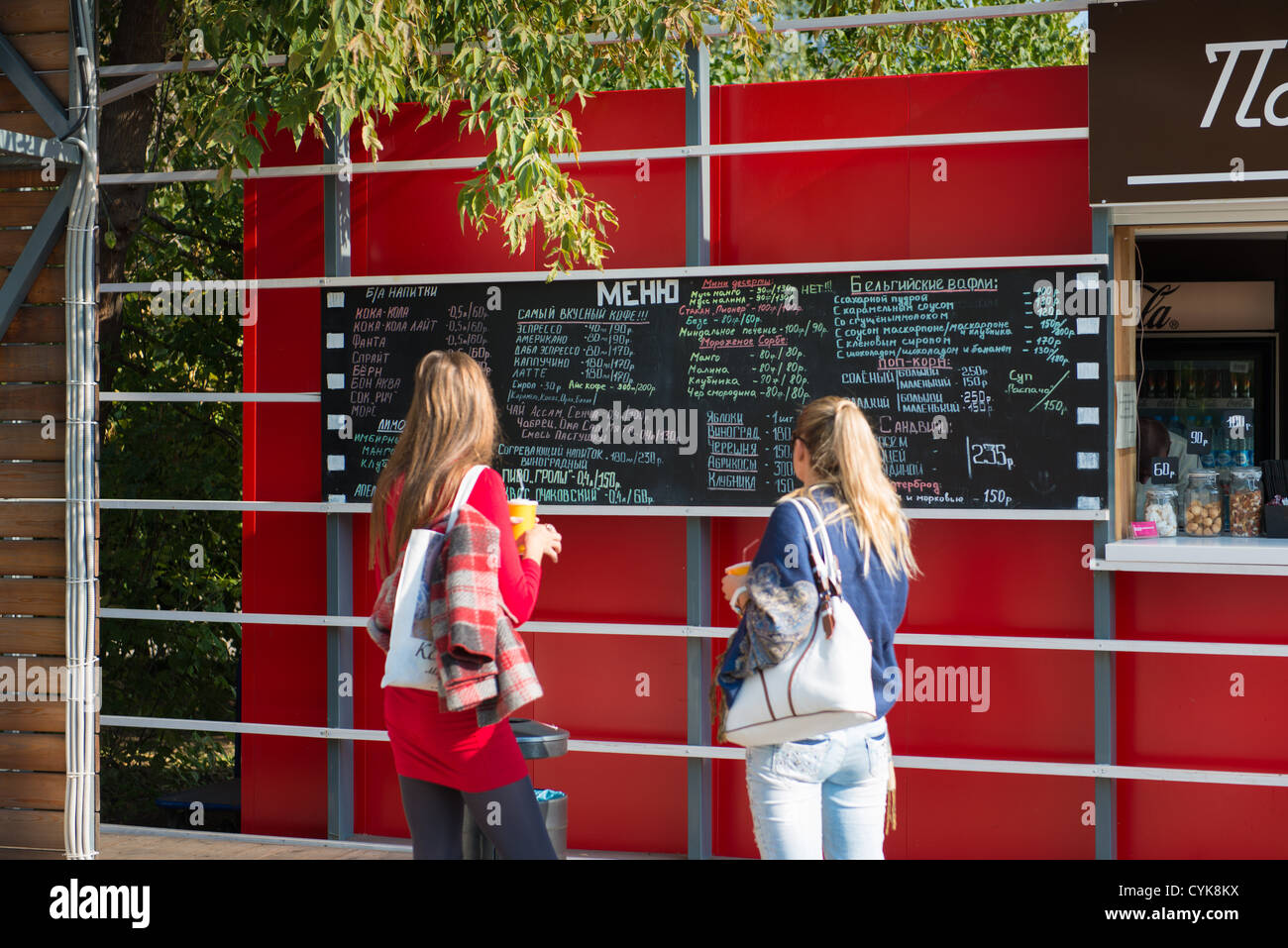 Girls read chalk board menu in Gorky park, Moscow - Stock Image