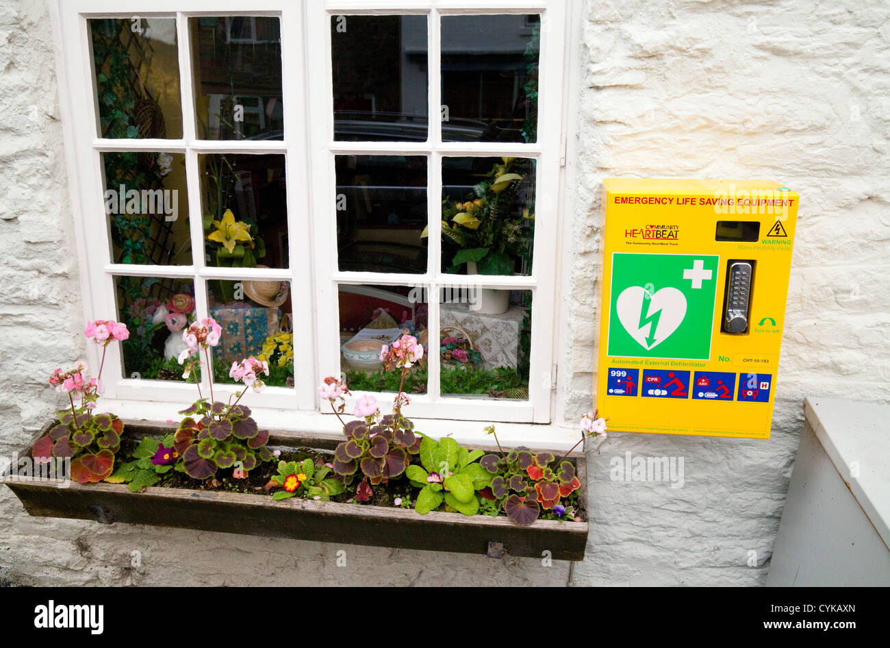 A cardiac heart defibrillator available to the public on the wall in Clun village, Shropshire UK - Stock Image