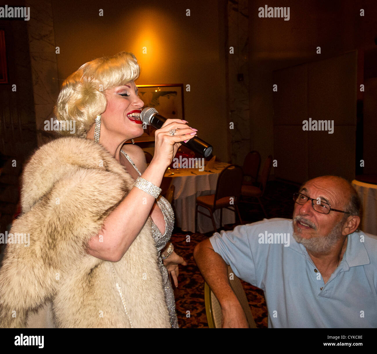 Marilyn Monroe impersonator sings to middle aged man at 1950s retro, art deco era party. - Stock Image