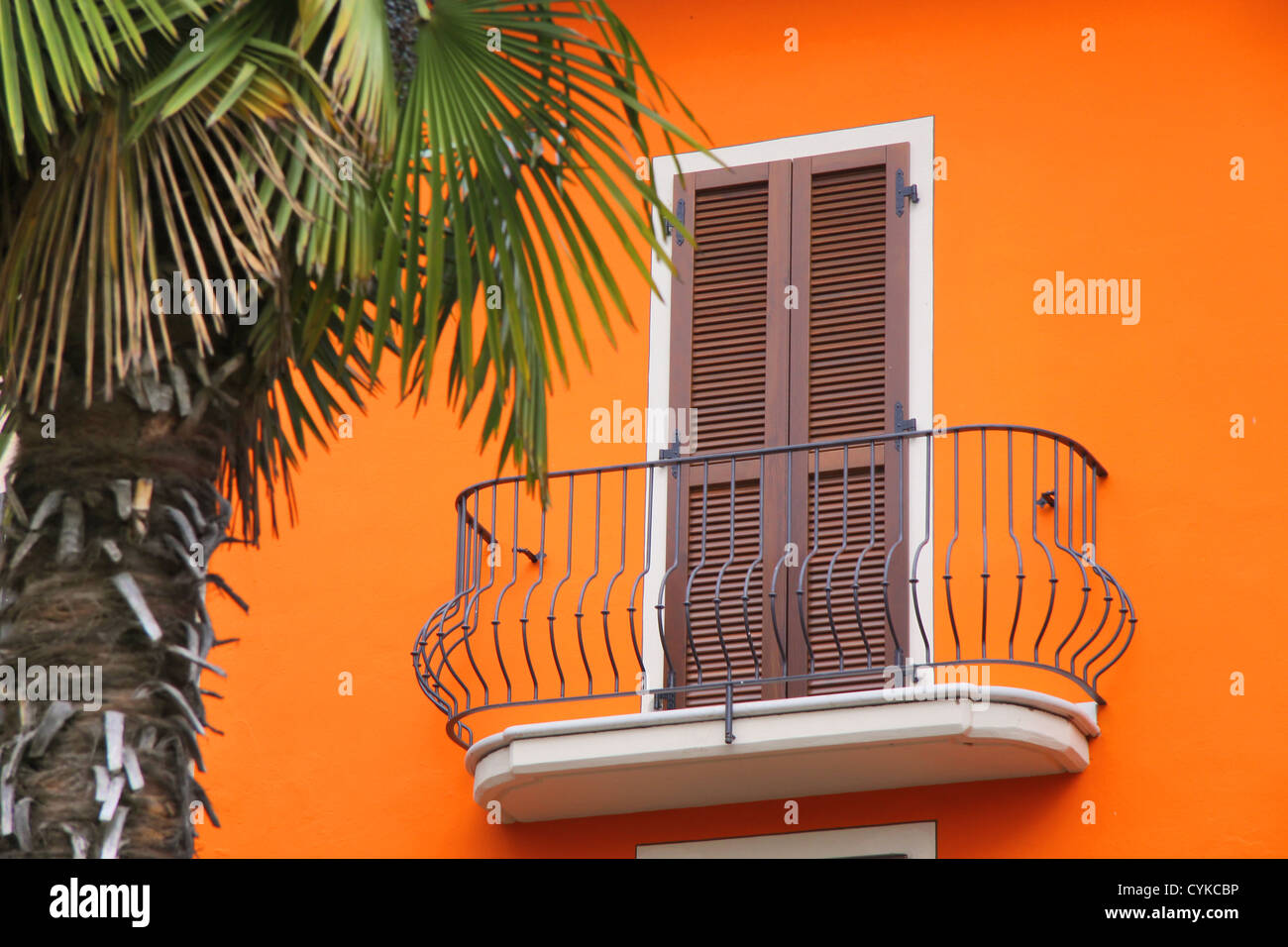Balcony of a house with an orange facade in Sirmione on Lake Garda, Region of Brescia, Lombardy, Italy - Stock Image