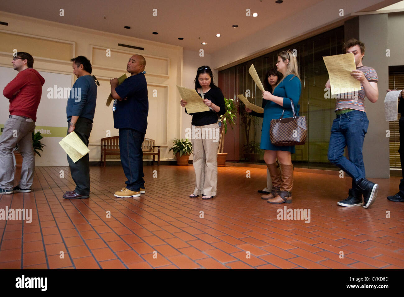 November 6th, 2012 Austin, Texas: Voters stand in line and review ballot waiting to cast their vote in Travis County - Stock Image