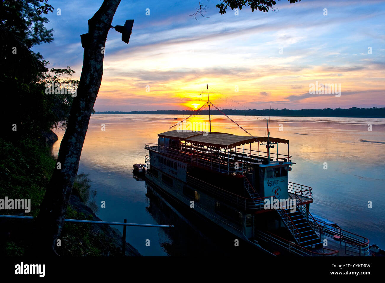 Sunset over the Amazon River and jungle and the River Boat, the Amazon Queen, docked in Peru or Brazil - Stock Image