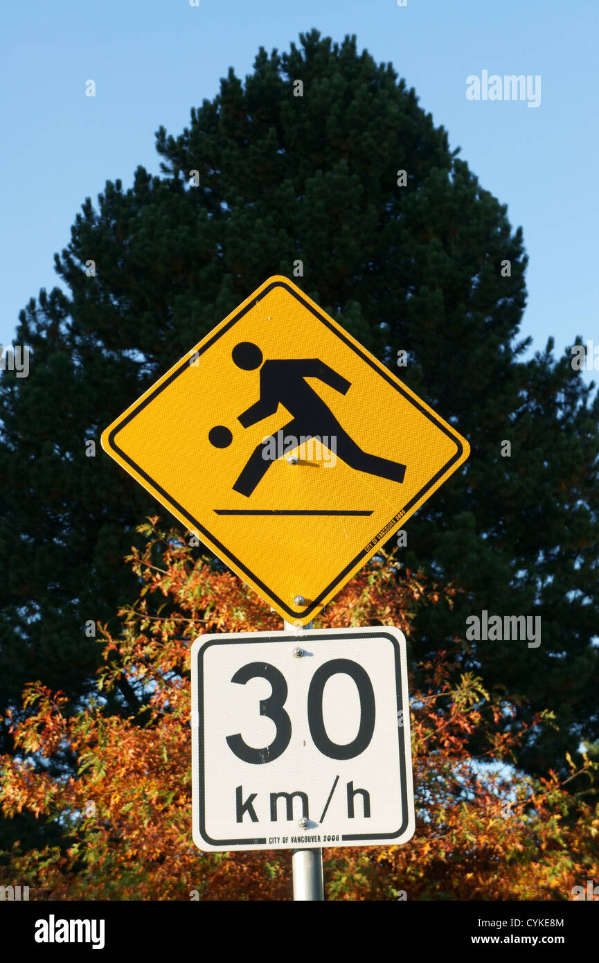 Children playing and speed limit road signs - Stock Image