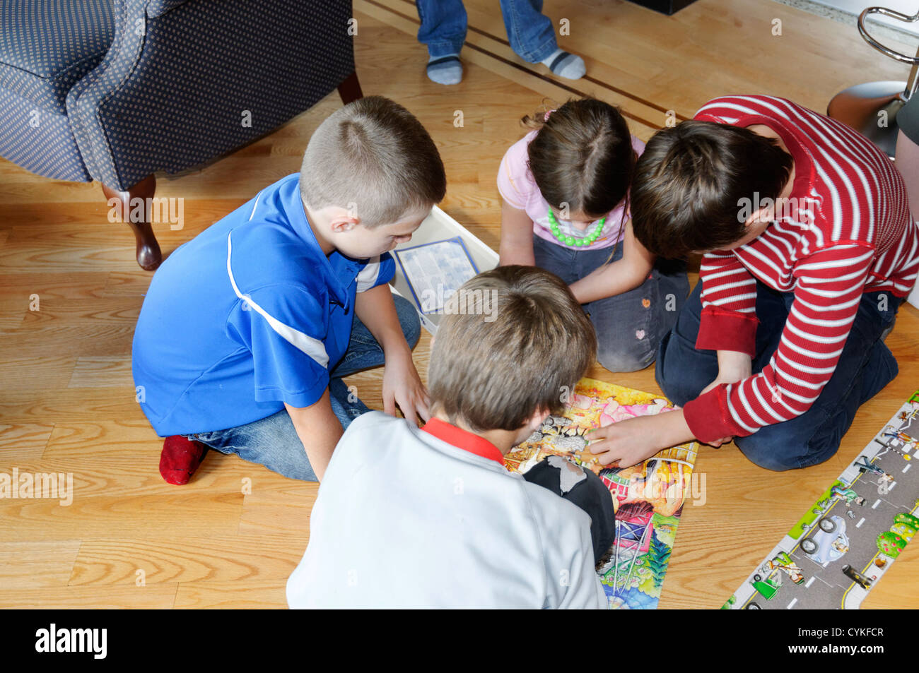 Four children doing a jigsaw puzzle - Stock Image