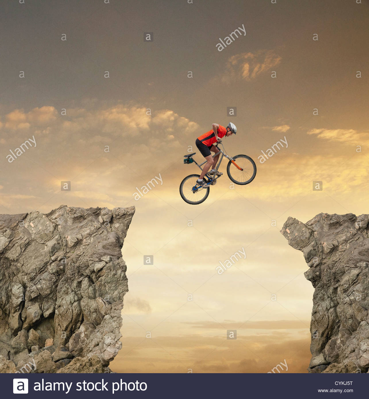 Mixed race bicyclist jumping over canyon Stock Photo