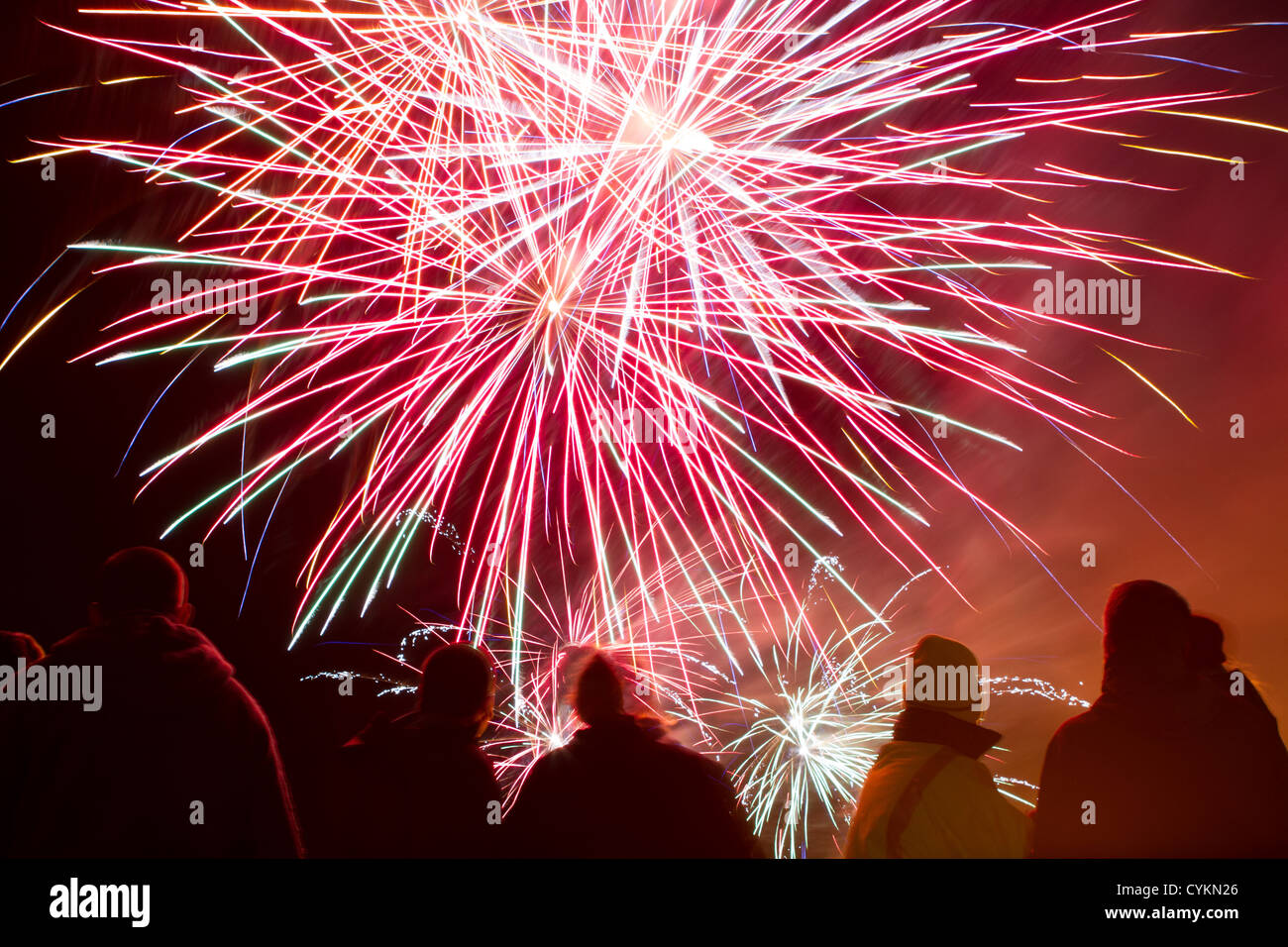 A crowd of people watch a fireworks display - Stock Image