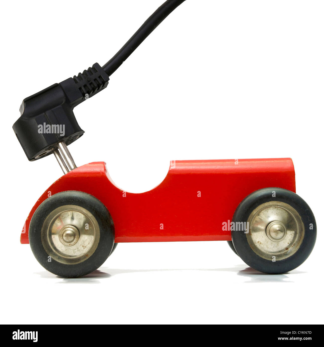 Small toy vehicle plugged in and charging using electricity plug concept - Stock Image