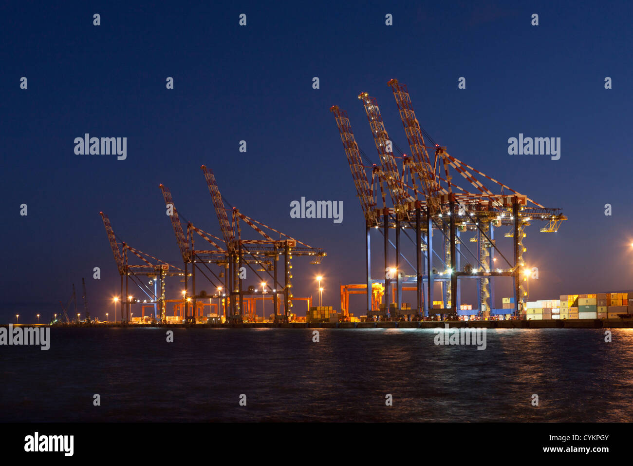 Cranes in shipyard lit up at night - Stock Image