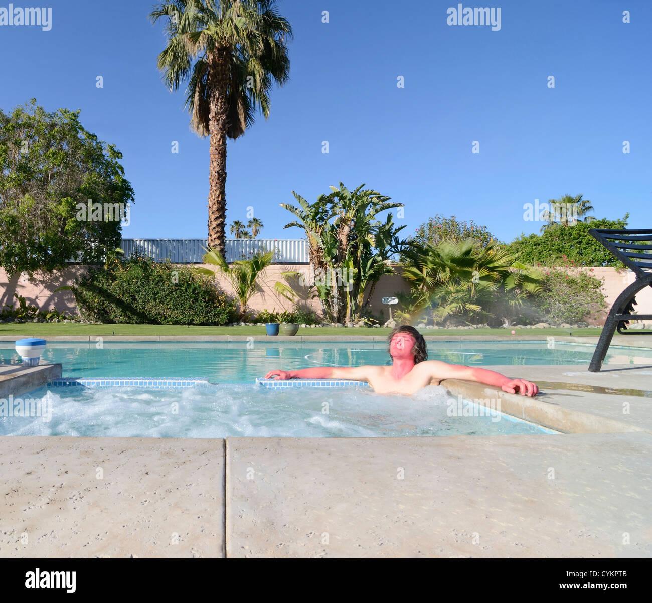 Sunburned man relaxing in hot tub - Stock Image