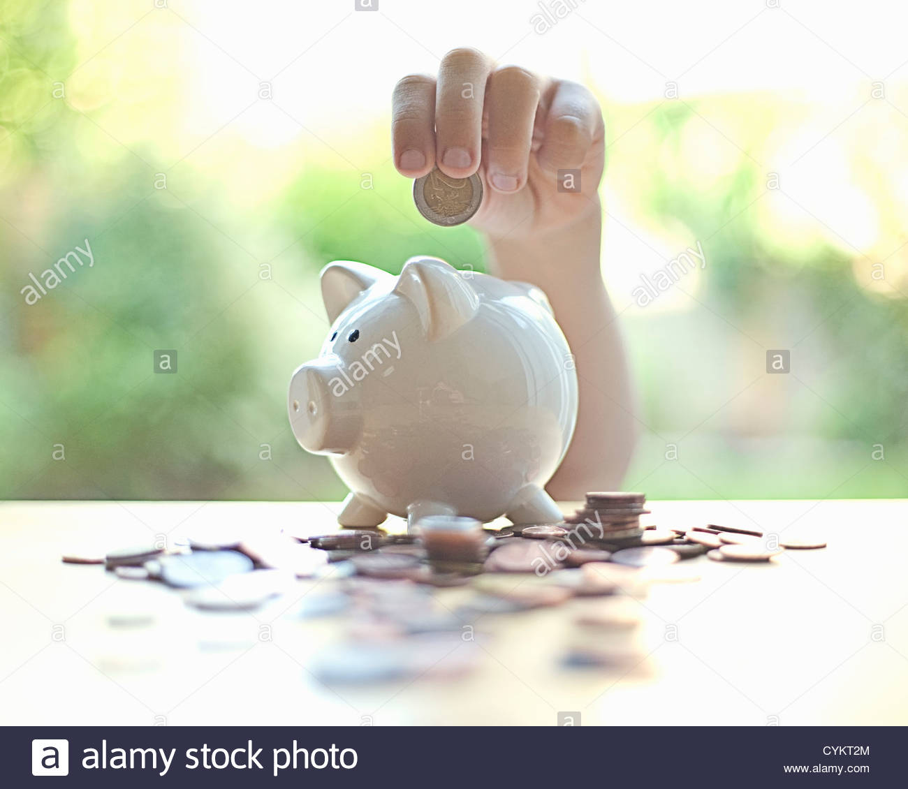 Hang putting coins in piggy bank - Stock Image