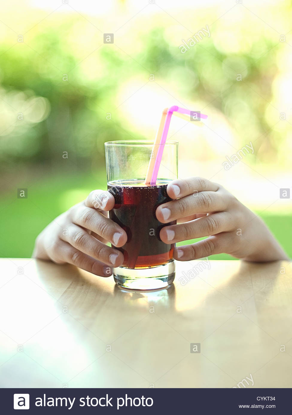 Hands reaching for glass of soda - Stock Image