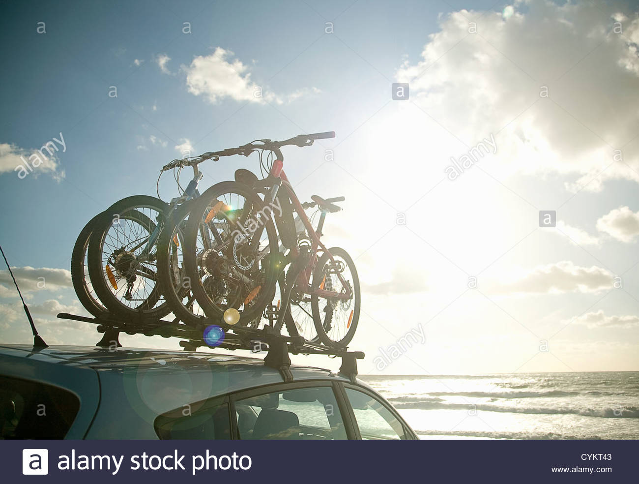 Bicycles attached to roof of car - Stock Image