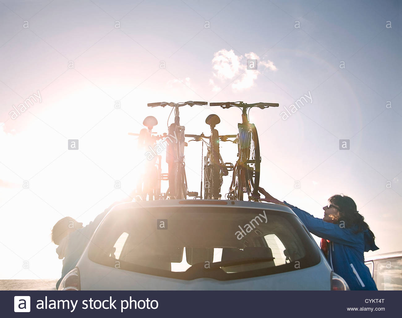 Mother and son tying bicycles on car - Stock Image