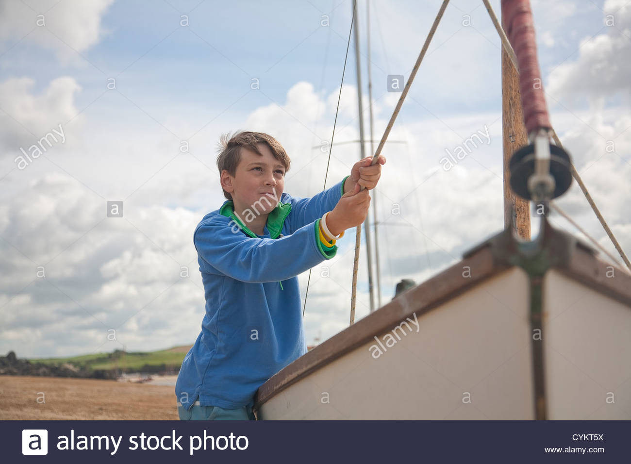 Boy pulling at sails on boat - Stock Image