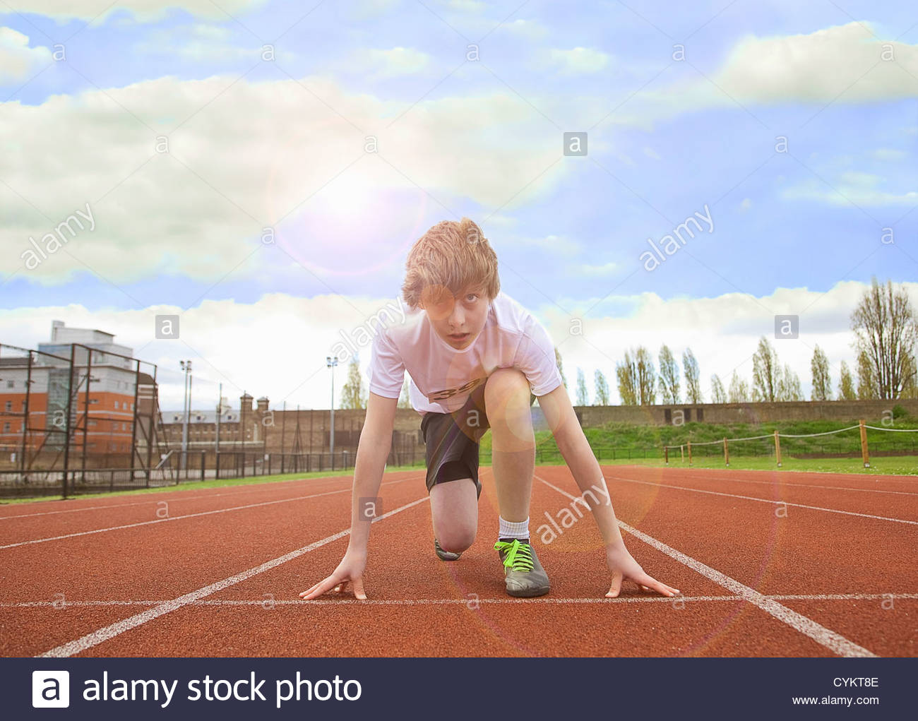 Boy crouched at starting line on track - Stock Image