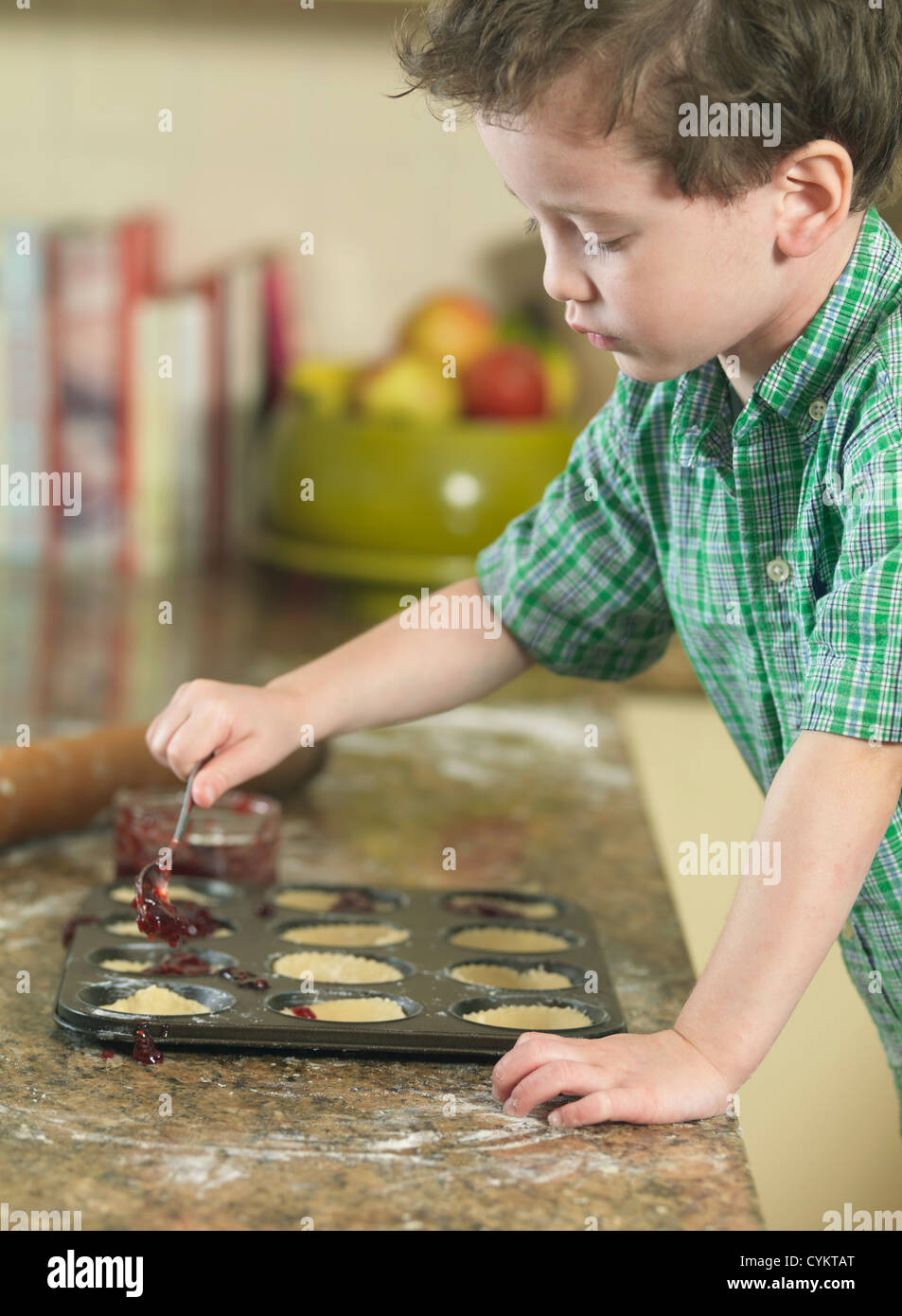 Boy spooning batter into pan in kitchen Stock Photo