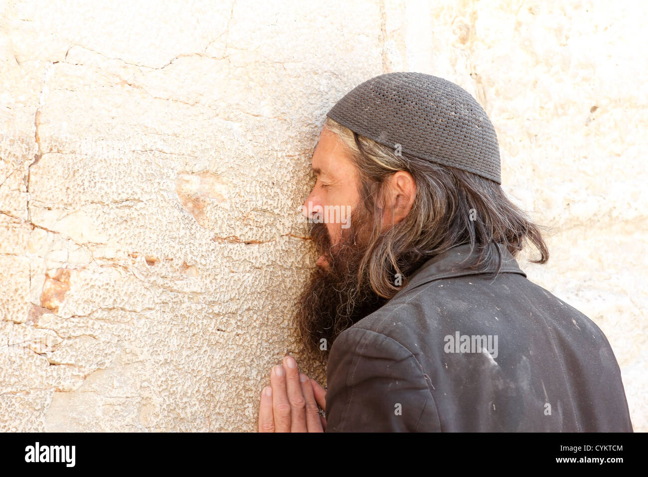 Jew is praying with his hands on the wailing wall in Jerusalem - Stock Image