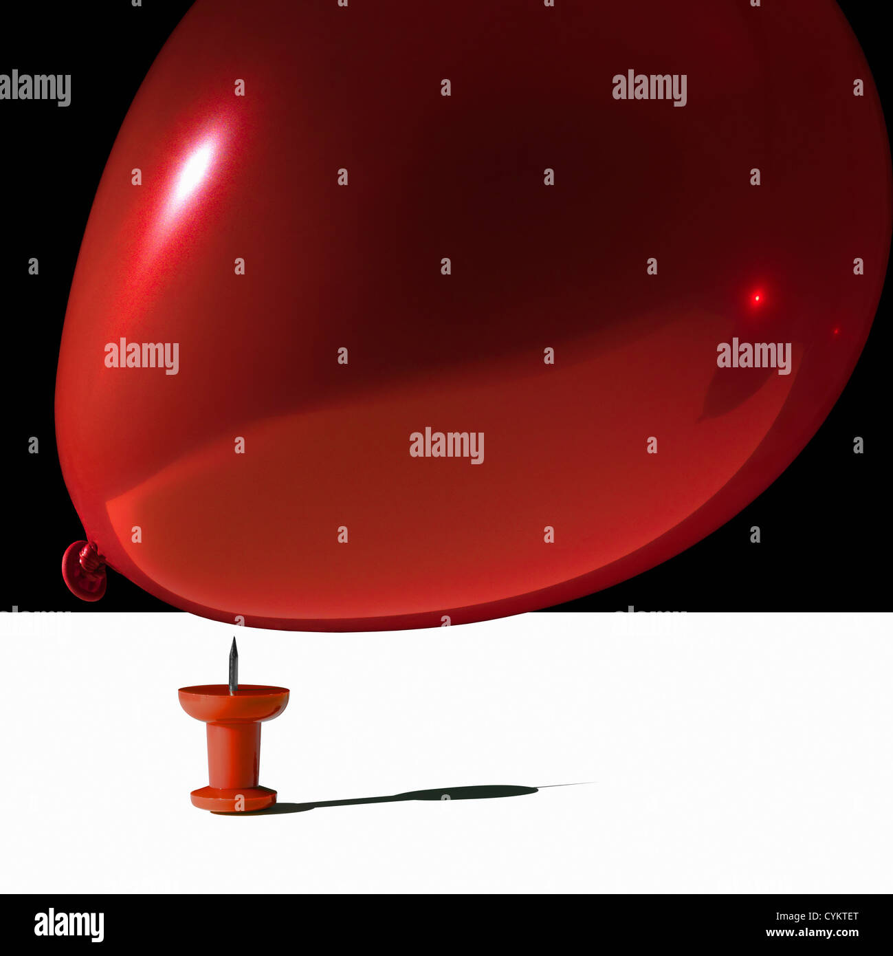 Balloon hovering over sharp pin Stock Photo