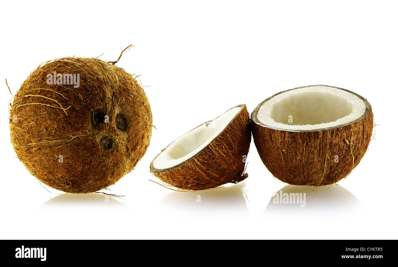 set of whole and cut coconuts over white background - Stock Image
