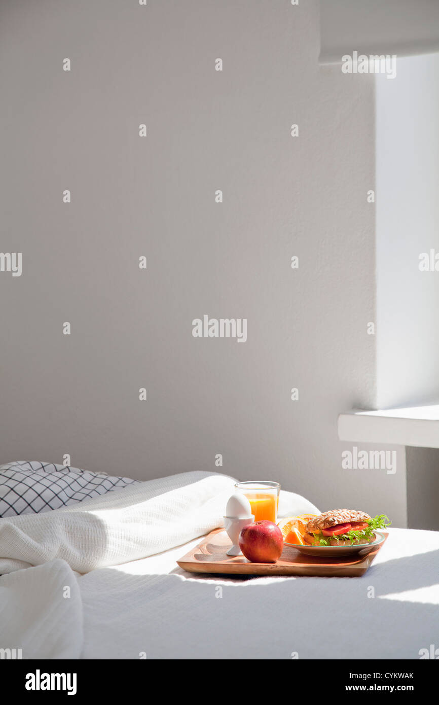 Tray of breakfast food on bed Stock Photo