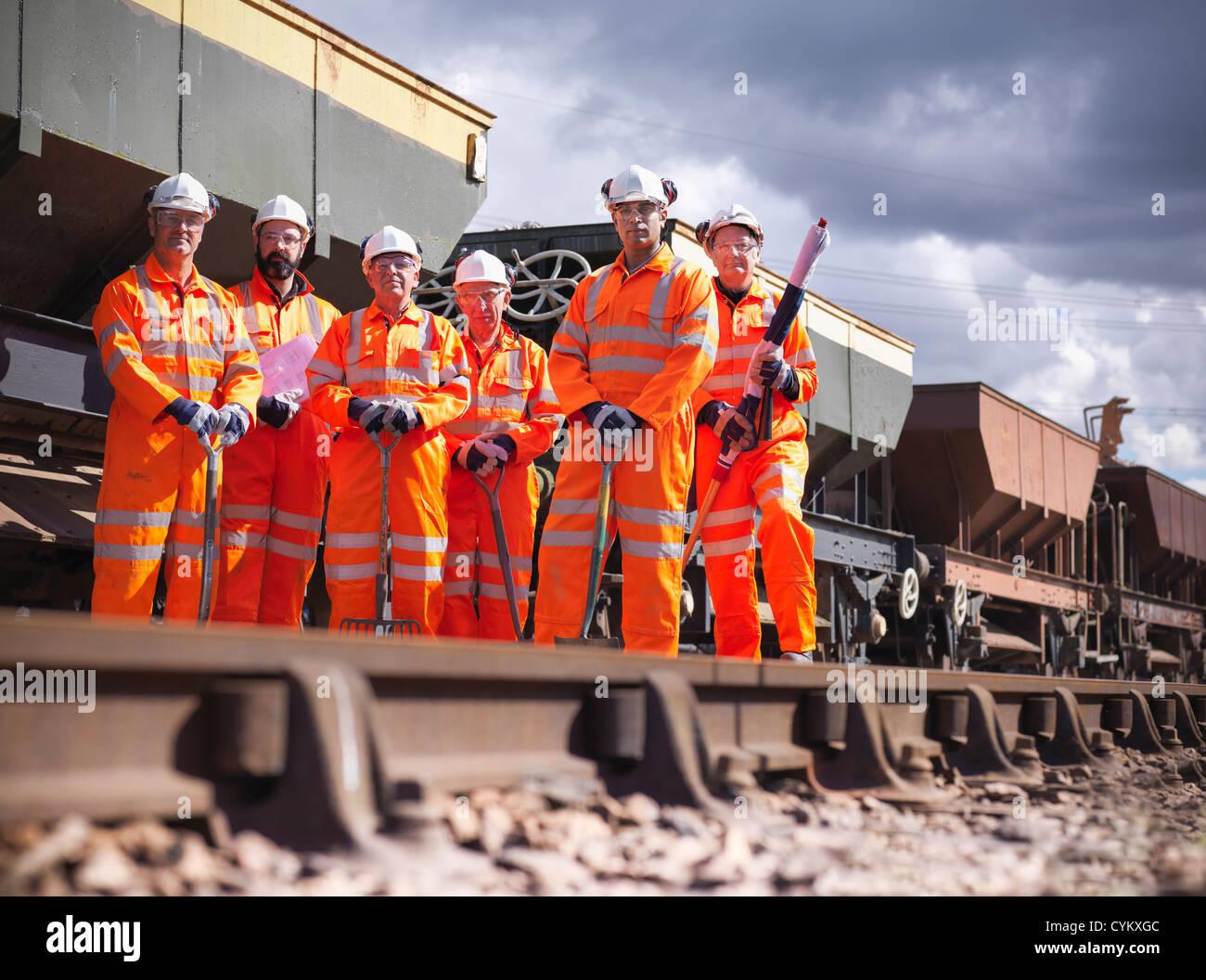 Railway workers standing on train tracks - Stock Image