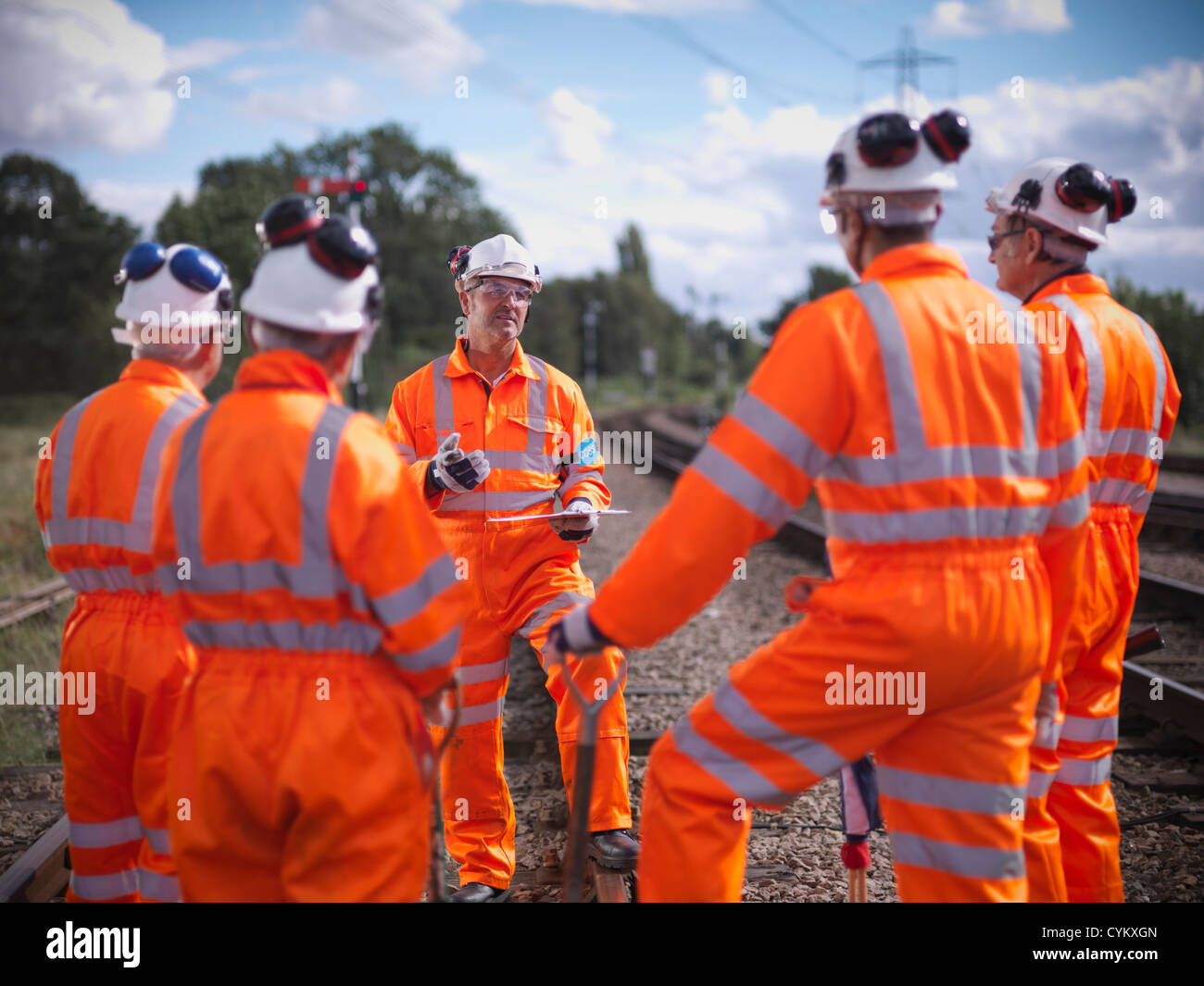 Railway workers talking on train tracks - Stock Image