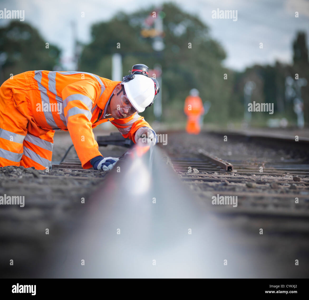 Railway worker examining train tracks - Stock Image