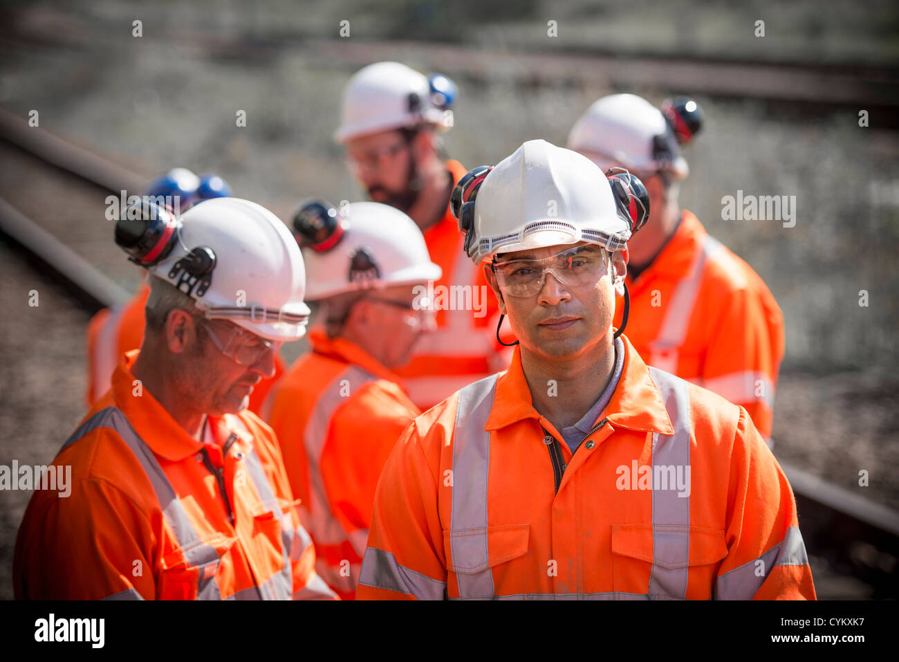 Railway workers standing on train tracks - Stock Image