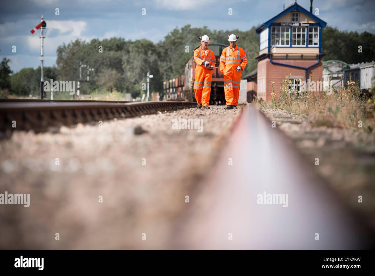 Railway workers walking on train tracks - Stock Image