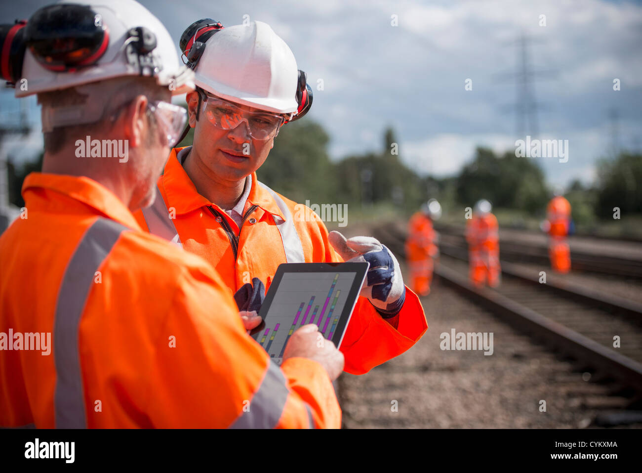 Railway workers using tablet computer Stock Photo