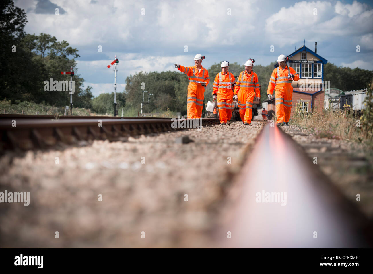 Railway workers walking on train tracks - Stock Image