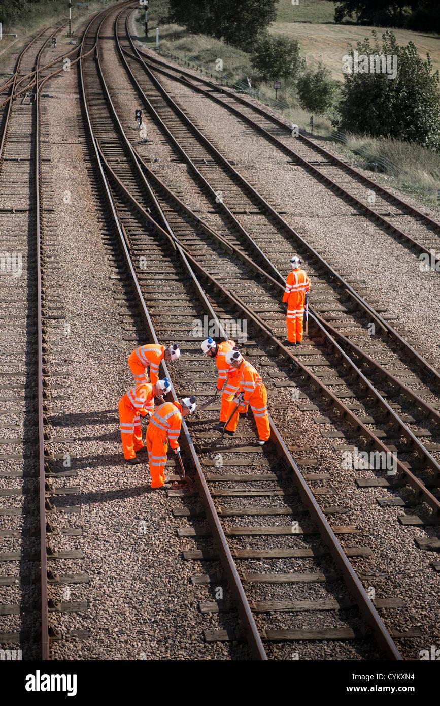 Railway workers examining train tracks - Stock Image