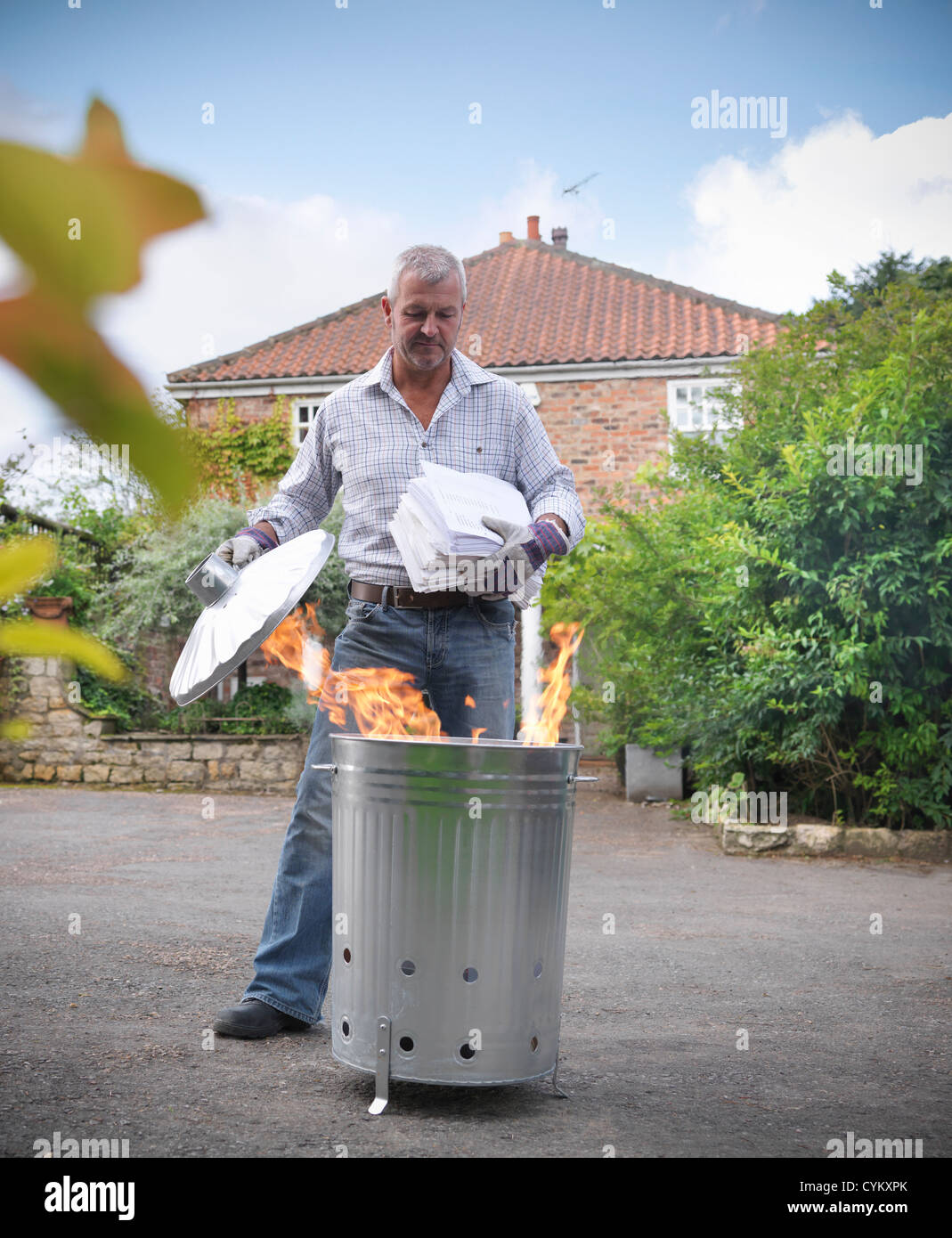 Man burning papers in garbage can - Stock Image