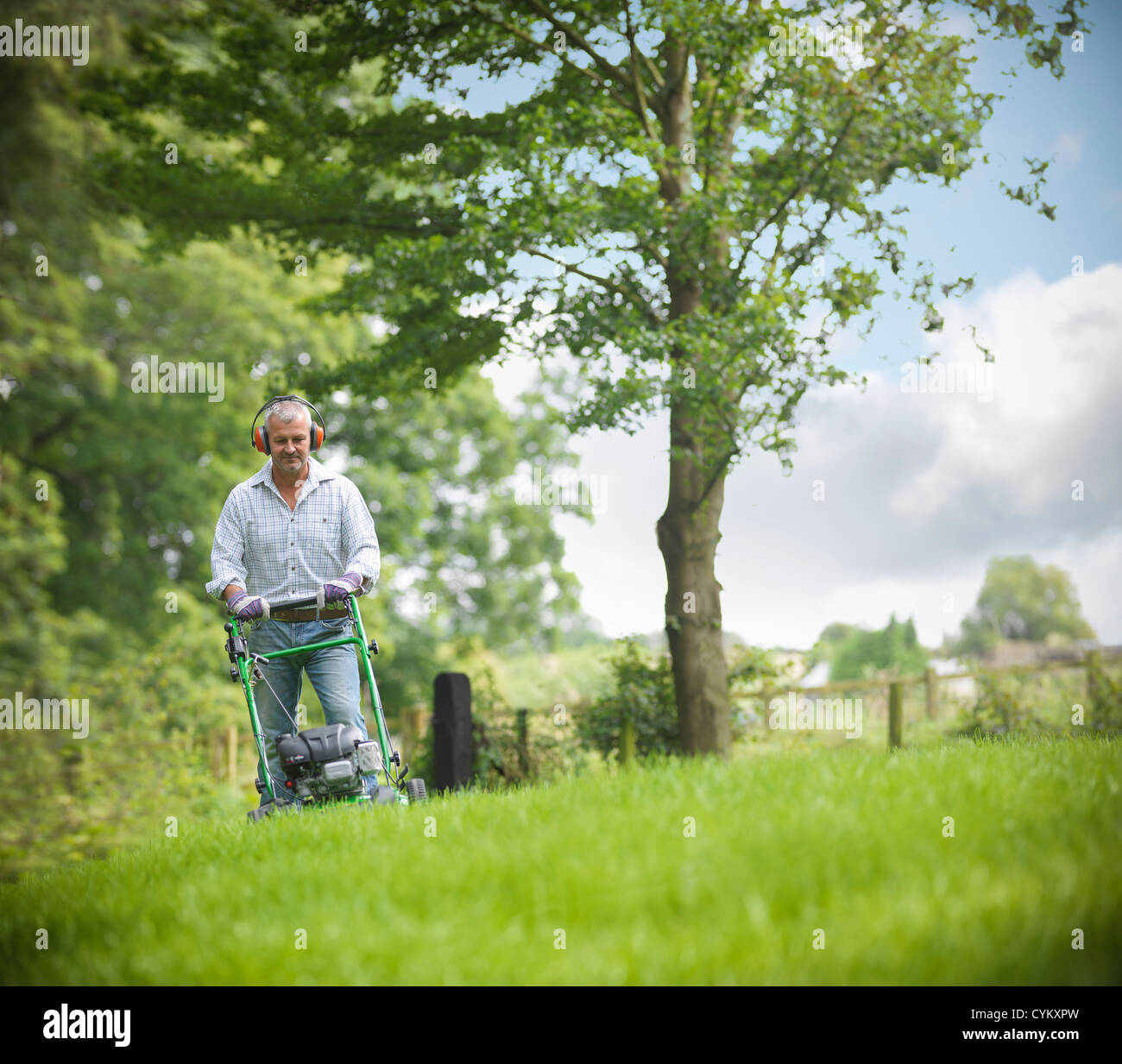 Man wearing headphones and mowing lawn - Stock Image