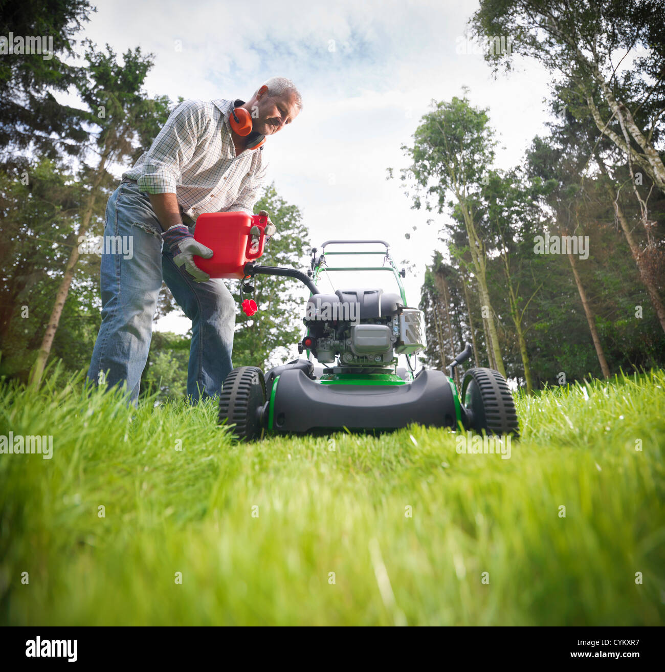 Man pouring gas into lawn mower - Stock Image