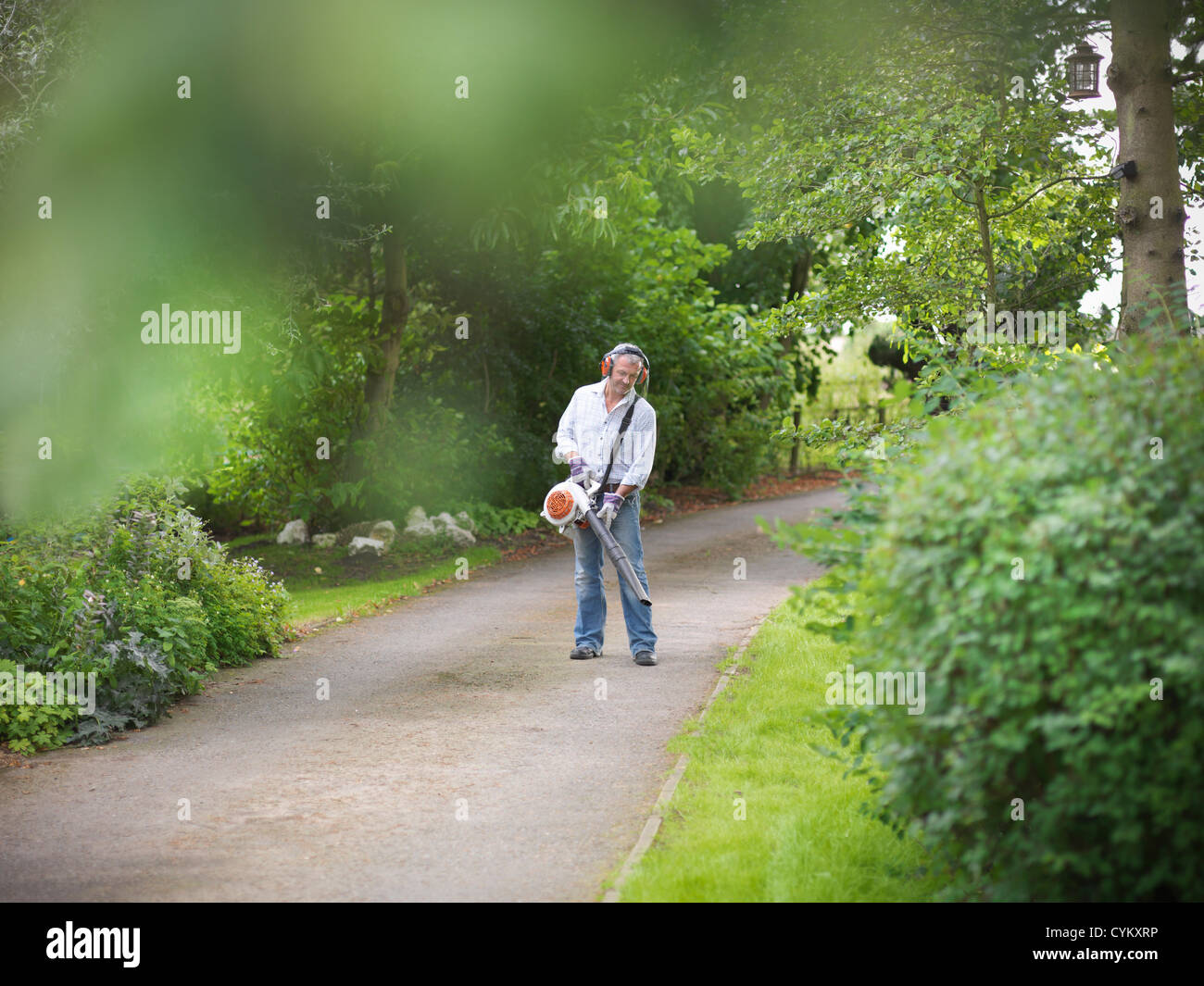 Man blowing leaves on paved road - Stock Image