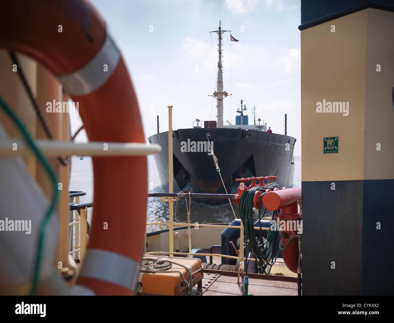 Tugboat pulling ship in ocean - Stock Image